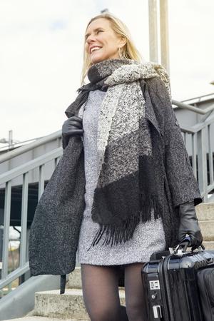down the stairs: mujer rubia con la maleta en la estación de tren para bajar escaleras y sonrisas