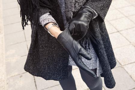 彼女の黒革手袋に通り入れて立っている女性をクローズ アップ