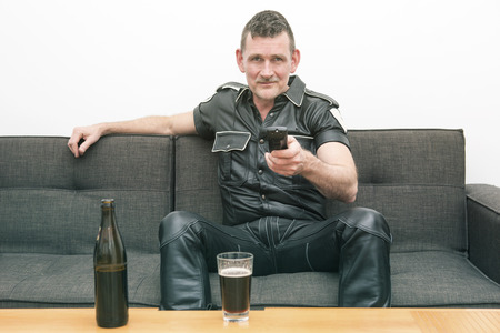 kinky: man wearing black fetish leather clothes and sitting on couch watching tv Stock Photo