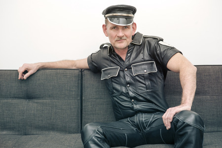fetish: man wearing black fetish leather clothes and sitting on couch Stock Photo