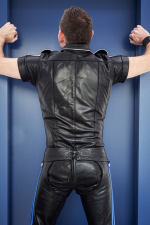backside of man wearing black fetish leather clothes