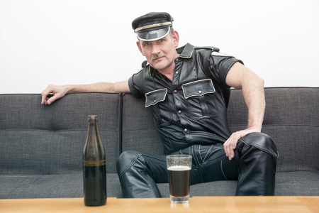 kinky: man wearing black fetish leather clothes,sitting on couch and drinking a beer