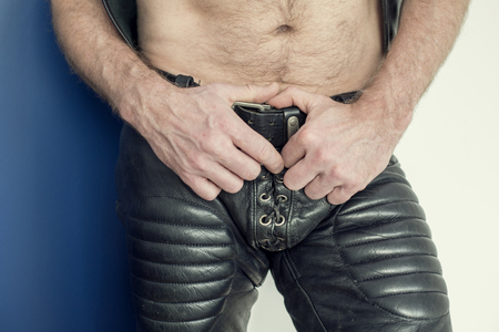 leather pants: close-up of man wearing black fetish leather pants