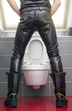 sm: backside of man wearing black leather fetish clothes standing at toilet