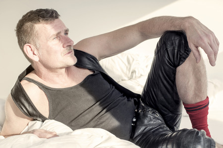 fetish: man in black fetish leather gear lying in bed