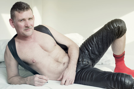 muscle guy: man in black fetish leather gear lying in bed and looking at camera