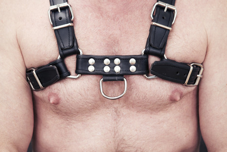 close-up of man wearing black leather fetish harness
