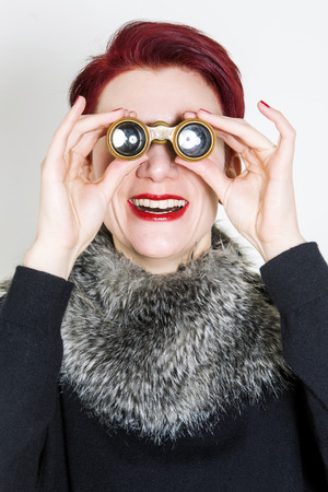 undercover agent: red-haired woman looking through binoculars and laughs Stock Photo
