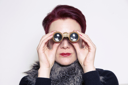 undercover agent: red-haired woman looking through binoculars Stock Photo