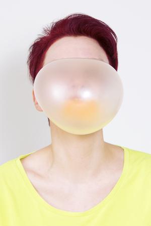 roodharige vrouw blaast een grote bel van kauwgom