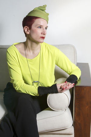 couch: portrait of red-haired woman with yellow hat sitting on couch