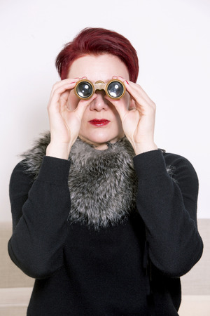 redhaired: red-haired woman looking through binoculars Stock Photo