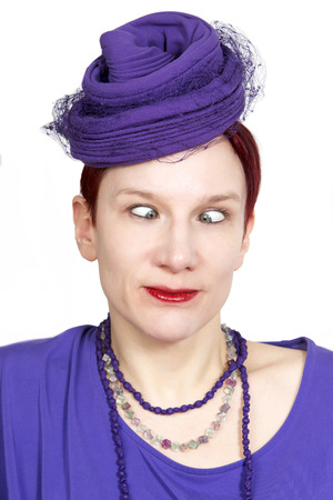 squint: portrait of cross-eyed red-haired woman with purple hat