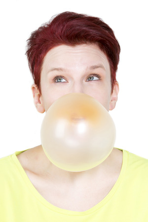 redhaired: red-haired woman blowing a big bubble of chewing gum Stock Photo