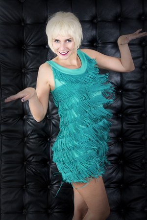 showgirl: blond showgirl in green dress is dancing in front of black leather background