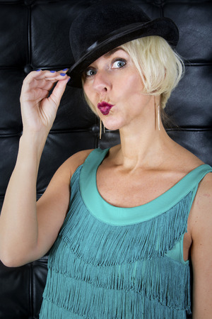 showgirl: blond showgirl in green dress wearing a black hat Stock Photo