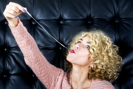 portarit: portarit of blond curly woman with bubblegum in front of black leather background