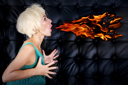 showgirl: blond woman in green dress spitting fire out of her mouth in front of black leather background