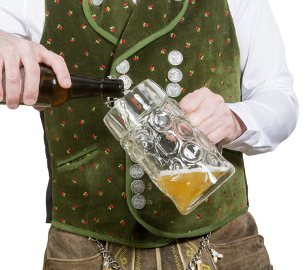 pouring beer: closeup of bavarian man pouring beer in a big mug
