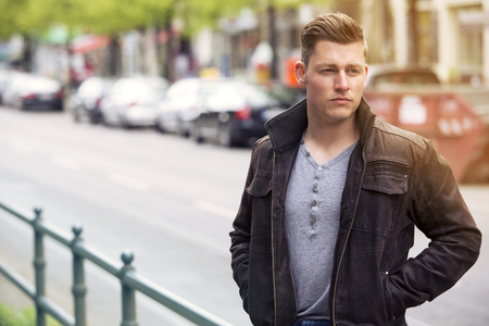 cocky: young blond man with leather jacket standing in the street Stock Photo