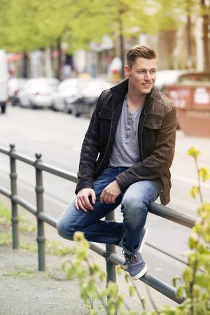 jeune homme blond avec veste en cuir assis à l'extérieur