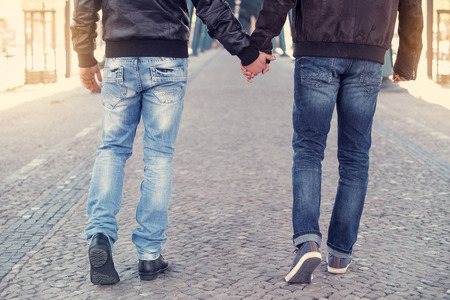 two men walking and holding hands