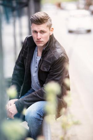 giovane biondo con giacca di pelle seduto fuori