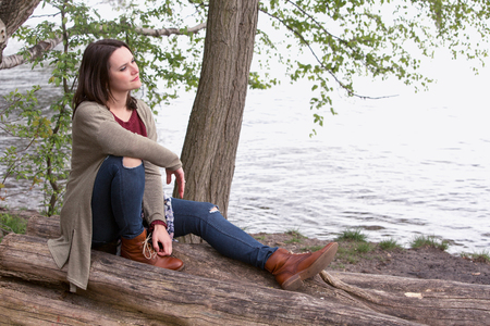 thoughtful woman: young woman sitting on a tree by the water and looking thoughtful Stock Photo