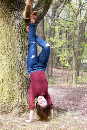 headstand: brunette woman making a headstand at a tree and pulling out her tongue