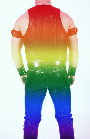 fetish: backside of a leathermen dressed in black fetish gear with rainbow colors for gay pride