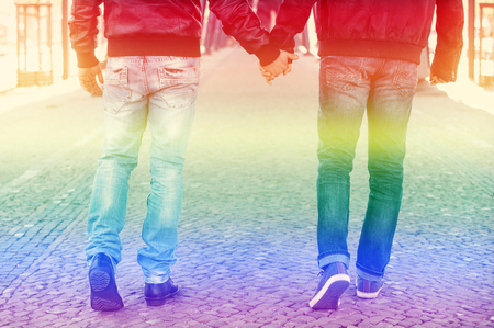 two men walking and holding hands with the rainbow colors for pride