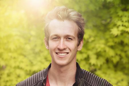 Ritratto di un giovane biondo in piedi fuori e sorridere alla telecamera