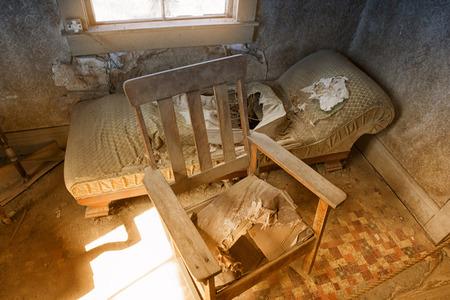 放棄された古い椅子が壊れ、不気味な部屋の中のソファ