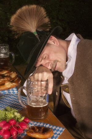 inebriated: bavarian man sitting at table and is drunk at Oktoberfest