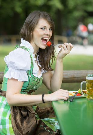 biergarten: young bavarian woman in dirndl sitting outside with beer mug and eating