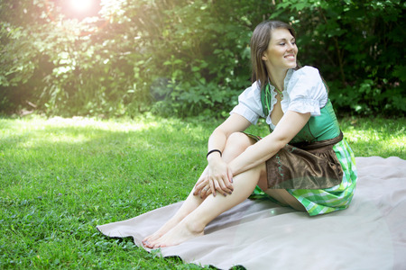 young bavarian woman in dirndl sitting on blanket outdoors
