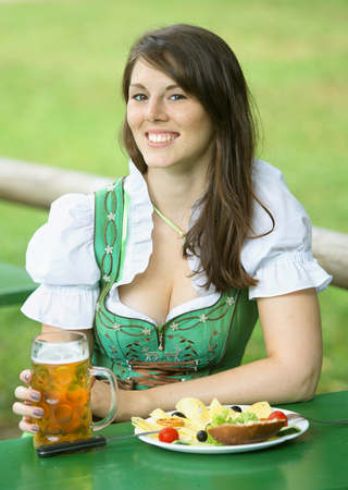 tracht: young bavarian woman in dirndl sitting at table in beer garden with beer and food
