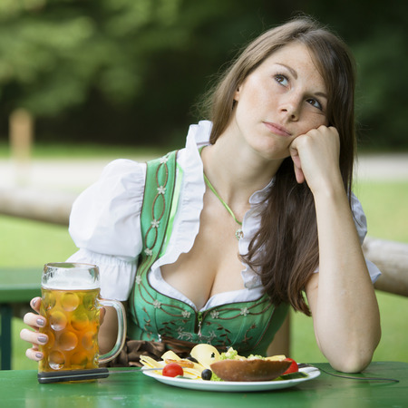 tracht: young woman in dirndl sitting at beer garden with food and beer and looking bored