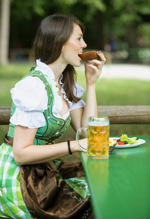 beer garden: young woman in dindl sitting at beer garden outdoors and eating bread