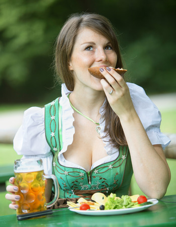 biergarten: young bavarian woman in dindl sitting outdoors at beergarden and eats Stock Photo