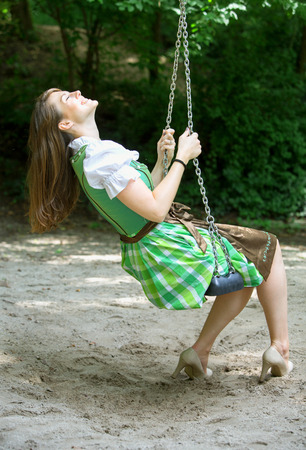 tracht: bavarian woman in dirndl sitting on swing at a playground
