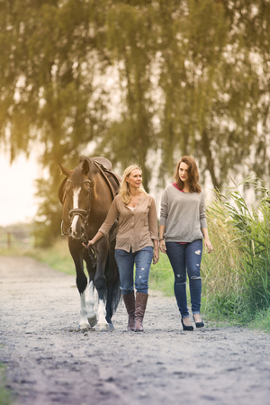 mum and daughter: two woman walking with horse on the countryside