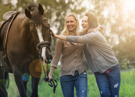 mum and daughter: two woman walking with horse at a farm Stock Photo