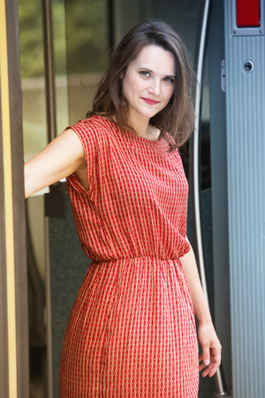 young woman in red dress standing in door of train wagon and looking at camera