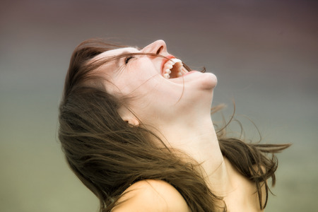 portrait of happy young brunette woman laughing with her eyes closed