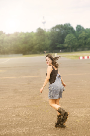 young brunette woman is rollerblading on a street