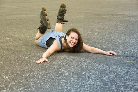 rollerblades: young woman with rollerblades lying on the street on her stomach and is laughing Stock Photo
