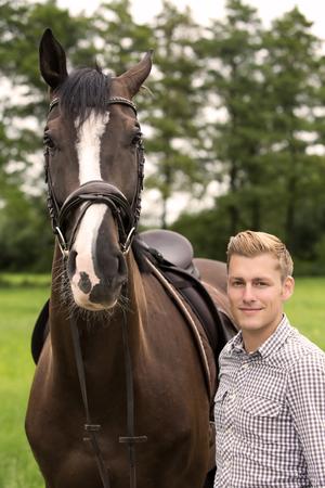 uomo a cavallo: l'uomo e il suo cavallo marrone su terreni agricoli
