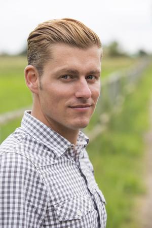 portrait d'un beau jeune homme blond dans la nature