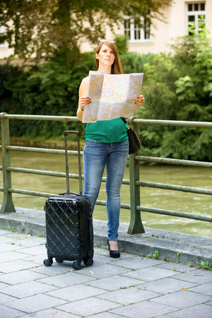 map case: young brunette woman standing with her suitcase and looking at a street map Stock Photo